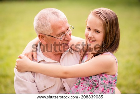 Smiling child hugging her happy grandfather - outdor in nature - stock photo