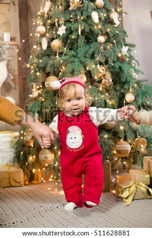 Smiling child in a cap of Santa Claus holding the christmas gifts