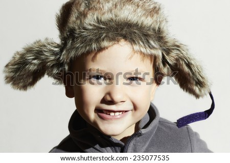 smiling child in fur Hat.fashion casual winter style.little funny boy.children emotion.hat ear flaps - stock photo