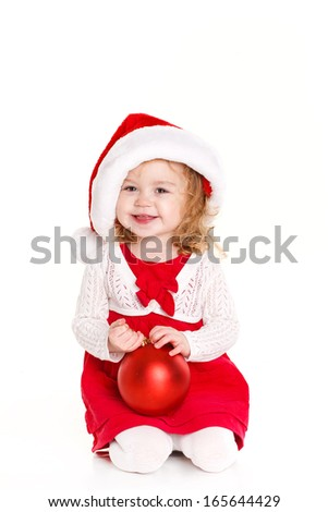 Smiling child in Santa hat holding Christmas decorations in hand isolated on white background