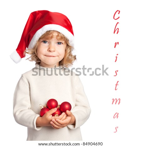 Smiling child in Santa hat holding Christmas decorations in hand isolated on white background - stock photo