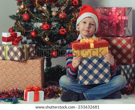 Smiling child in Santa red hat holding Christmas gifts in hands.  New Year's holidays. - stock photo