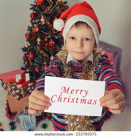 Smiling child in Santa red hat holding Christmas greeting card in hands. Christmas concept. Selective focus - stock photo