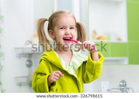 Smiling child kid girl brushing teeth in bathroom - stock photo