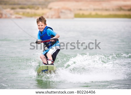 Smiling Child learning to wake-board - stock photo