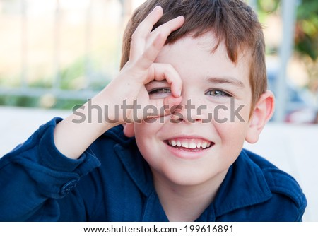 Smiling child looking through his fingers - stock photo
