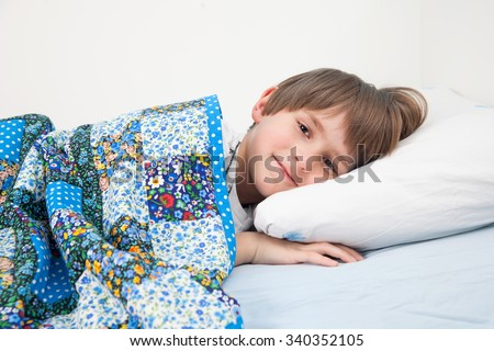 smiling child lying in bed under a patchwork quilt - stock photo