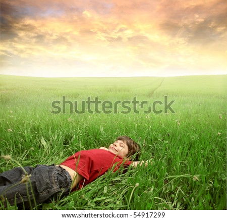 Smiling child lying on a green meadow - stock photo