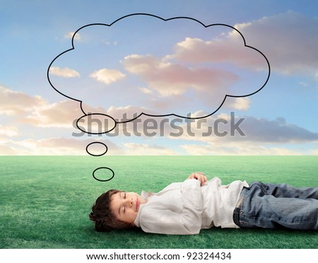 Smiling child lying on a green meadow with balloon over his head - stock photo