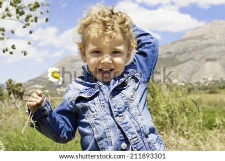 smiling child playing with a flower in the field standing - stock photo