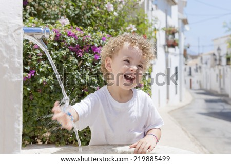 smiling child playing with the water from a fountain on a hot summer day in Altea - Alicante - Valencian Community - stock photo