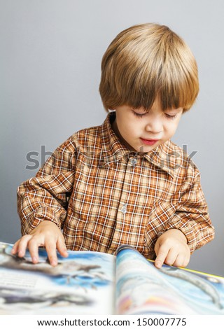 Smiling child reading a book - stock photo