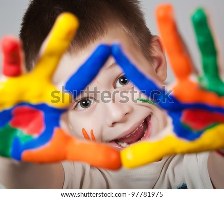 Smiling child showing his colored hands
