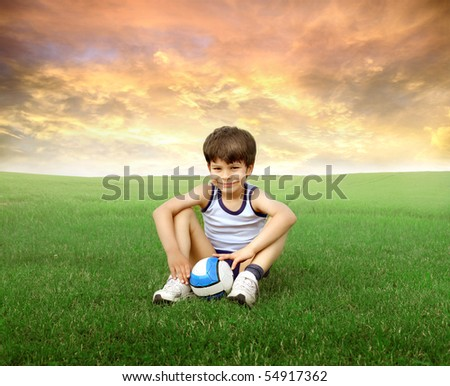 Smiling child sitting on a green meadow with a football in front of him - stock photo