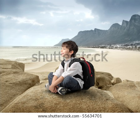 Smiling child sitting on a rock with seascape on the background - stock photo
