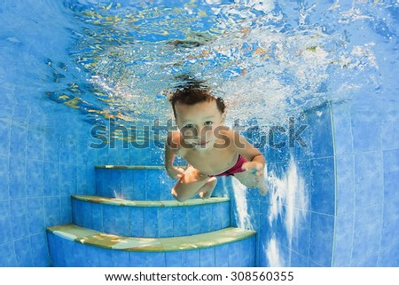 Smiling child swimming with fun - jump underwater and dive in outdoor pool. Healthy family lifestyle, water sport activity and physical exercises with active parents on summer holidays with baby boy - stock photo