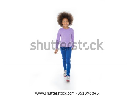 smiling child walking and looking at the camera  - stock photo