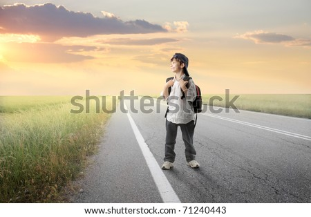 Smiling child with backpack walking on a countryside road - stock photo