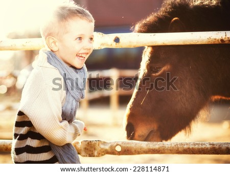 Smiling child with pony in the mini zoo - stock photo