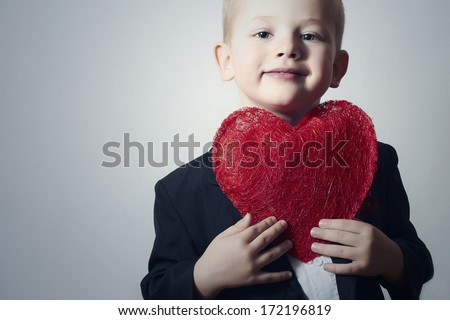 Smiling Child with Red Heart. Four Years Old Handsome Boy with Heart Symbol. Lovely Kid in Black Suit Valentine's Day - stock photo