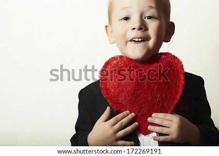 Smiling Child with Red Heart. Funny Boy with Heart Symbol. Lovely Kid in Black Suit Valentine's Day for Mother - stock photo