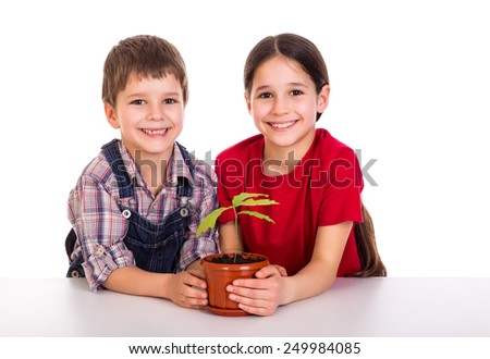 Smiling children caring for potted plant, isolated on white - stock photo