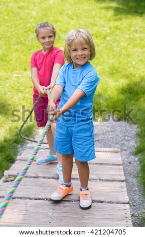 Smiling children  climbing on outdoor playground - stock photo