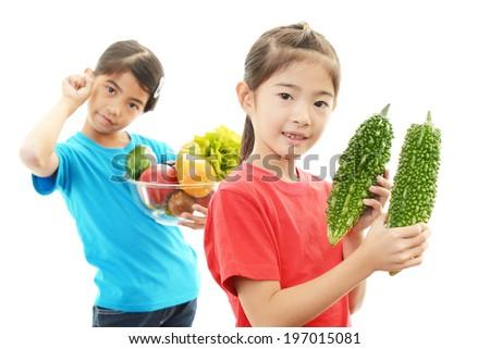 Smiling children holding vegetables  - stock photo