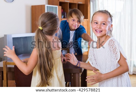 smiling children playing romp game Touch-last at home - stock photo
