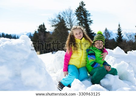 Smiling children playing with snow on a sunny day in winter mountains  - stock photo