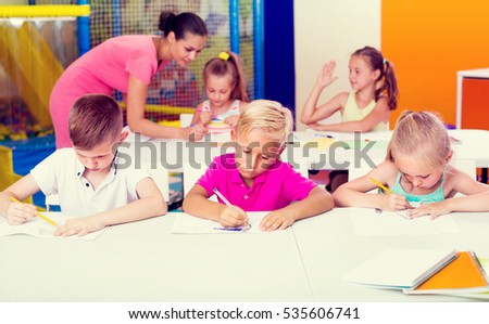 smiling children sitting together and studying in class at school