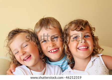 Smiling children three together in cozy, girl at left closed eyes