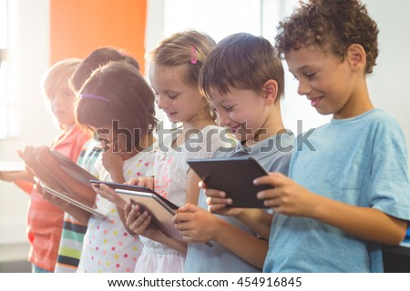 Smiling children using digital tablets in classroom