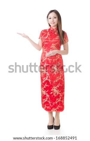 Smiling Chinese woman dress traditional cheongsam and introduce on white background. - stock photo
