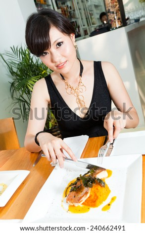 Smiling chinese young women sitting in a restaurant - stock photo