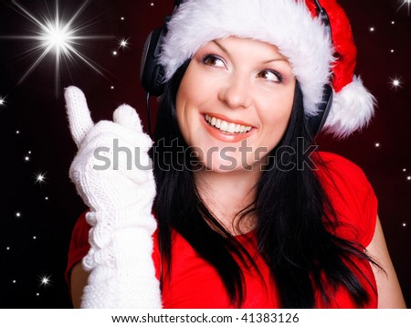 smiling christmas with headphones woman pointing star over red background - stock photo