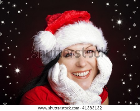 smiling christmas woman in santa cap with stars over red background