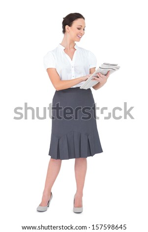 Smiling classy businesswoman holding newspaper while posing on white background - stock photo