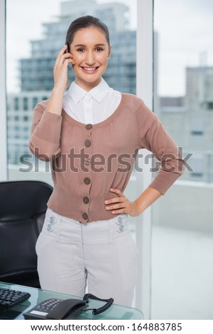 Smiling classy businesswoman on the phone in bright office - stock photo