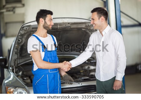 Smiling client and mechanic shaking hands in sevice - stock photo