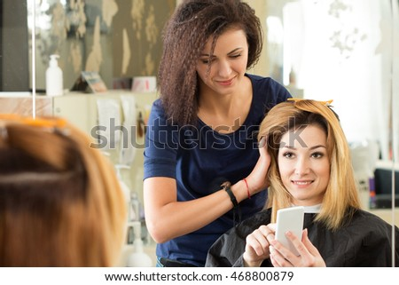 Smiling client showing her hairdresser on mobile phone what haircut she wants to do. Healthy hair, latest hair fashion trends, changing haircut style concept