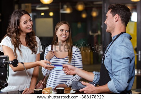 Smiling clients paying with card at the bar - stock photo