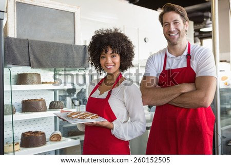 Smiling co-workers posing with desert at the bakery - stock photo