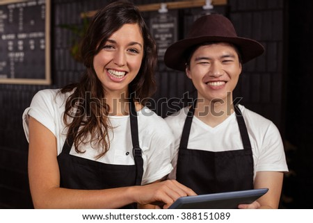 Smiling co-workers using tablet at the coffee shop - stock photo