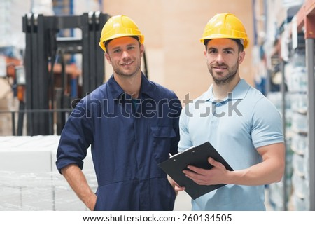 Smiling colleague posing with clipboard in warehouse - stock photo