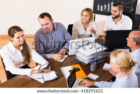 smiling  colleagues discussing price development at office - stock photo