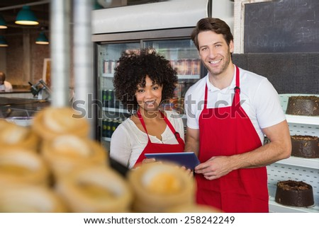 Smiling colleagues holding tablet pc at the bakery - stock photo