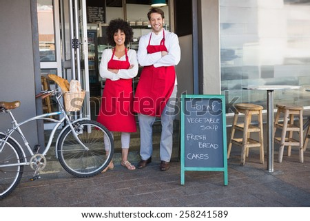 Smiling colleagues in red apron with arms crossed at the bakery - stock photo