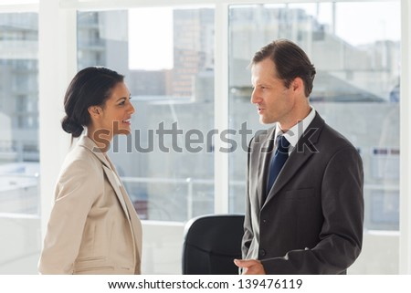Smiling colleagues speaking together in an office