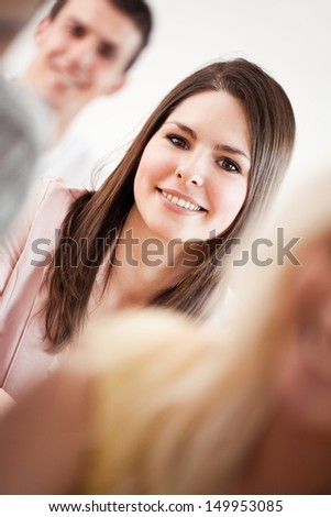 Smiling college students sitting together. - stock photo